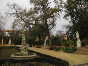 La plaça dels Quatre Continents, amb les escultures de Virginio Arias representatives d'Europa, Àsia, Àfrica i Amèrica; també es veu el gran roure pènol catalogat. Fotografia de Maria Josep Tort