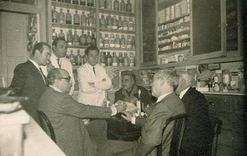 Tertúlia a la rebotiga, els anys cinquanta. D'esquerra a dreta, el fotògraf M. Coria, J. Fluvià, Enrique, Joaquin, el pintor Mercader,  Roure i l'arquitecte Sixte. Fotografia de la farmàcia Caldés.