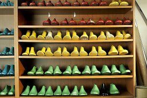 Una prestatgeria amb mostres d'alces de calçats. A la imatge destacada, Francesc Coher fent feina al taller on ha reunit maquinària especialitzada molt moderna. Fotografies de Javier Sardá
