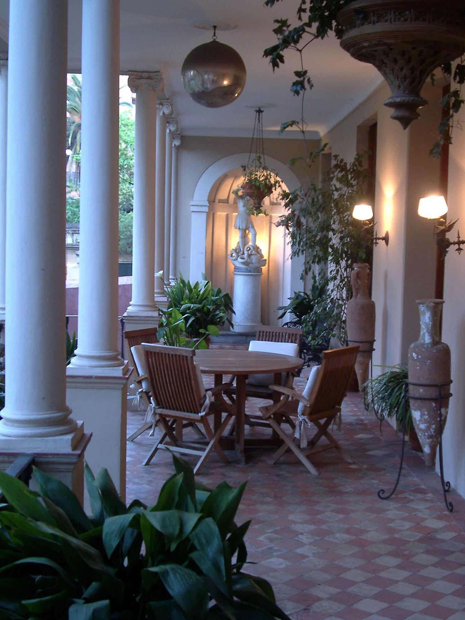 A dalt, vista frontal de la façana posterior de la casa, des de jardí. A primer plà, el sortidor. A sobre, vista de la galeria, amb peces artístiques i vegetació d'interior.